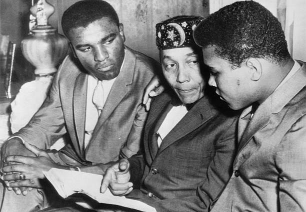 Heavyweight boxing champion Cassius Clay (R) and his brother Rudy (L) speaking with the leader of the Nation of Islam Elijah Muhammad Poole.