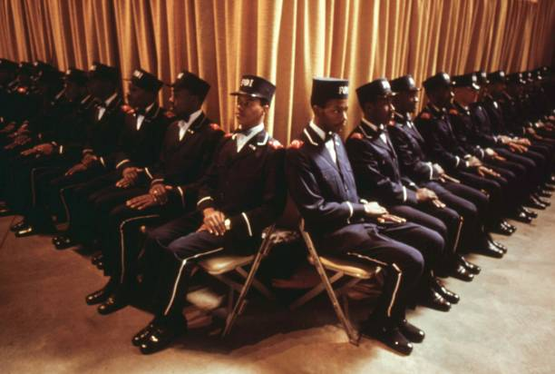 The Fruit of Islam, a group of bodyguards for Muslim leader Elijah Muhammad, sit by as he delivers his annual Savior's Day message in Chicago, Illinois, 1974. Image courtesy John White/US National Archives. (Photo via Smith Collection/Gado/Getty Images).