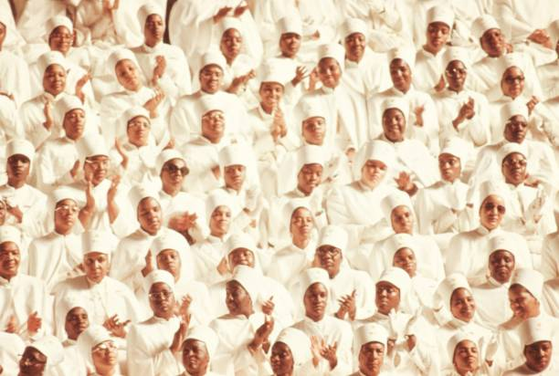 Black Muslim women dressed in white garb applaud Elijah Muhammad during his annual Savior's Day Message in Chicago, Illinois, 1974. Image courtesy John White/US National Archives. (Photo via Smith Collection/Gado/Getty Images).
